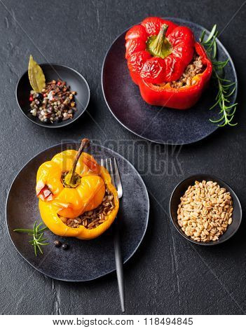 Baked stuffed bell peppers filled with spelt wheat, rice, vegetables Stone background