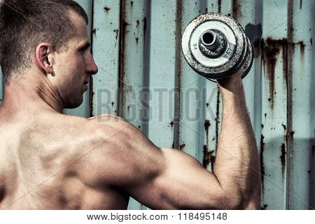 Close Up Young Athletic Man Doing Workout With Heavy Dumbbell Against The Background Of Agray Metal