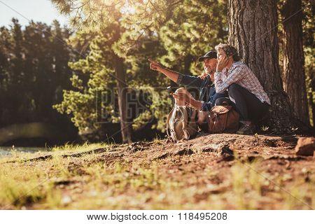 Mature Sitting Near A Lake Using Compass