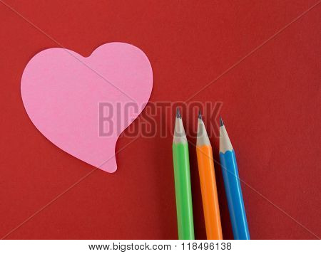 Pink Heart-shaped Memorandum On Red Paper With Colorful Pencils