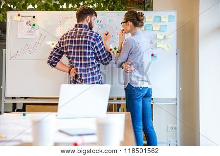 Young woman and man discussing about business strategy in office