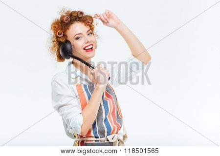 Happy redhead housewife with curly hair in apron posing with soup ladle isolated on a white background