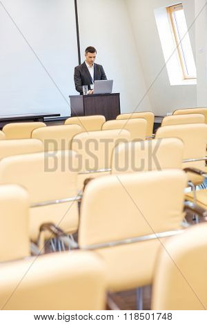 Pensive focused businessman standing on tribune and using laptop in empty meeting hall