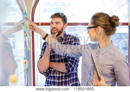 Casual business people working with whiteboard in office