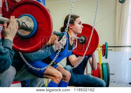 female athlete of powerlifter squats barbell