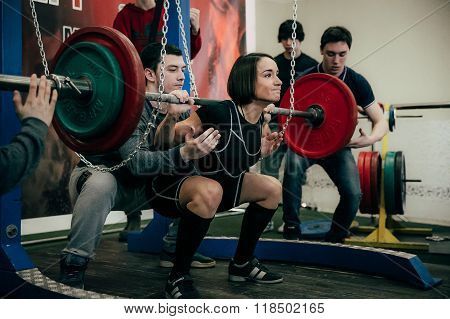 young woman athlete of powerlifter squats barbell