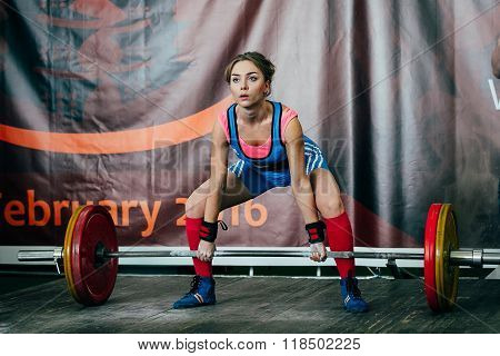 young woman athlete performs deadlift barbell