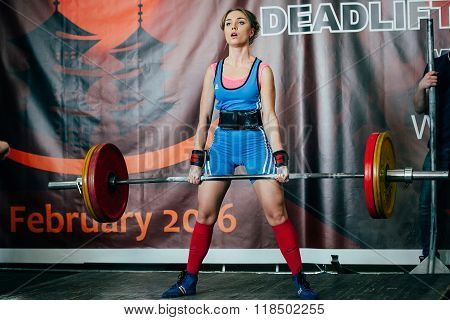 woman athlete performs successful deadlift barbell
