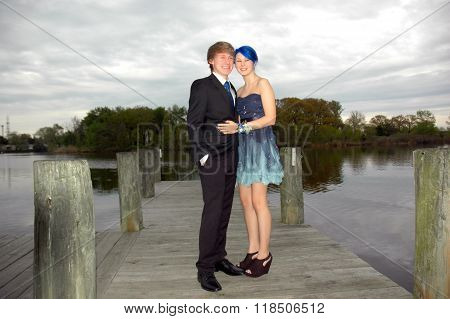 Young teen couple pose for prom photo on pier near river.