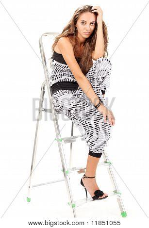 junge Frau im Harem Pants posiert mit Trittleiter auf weiß