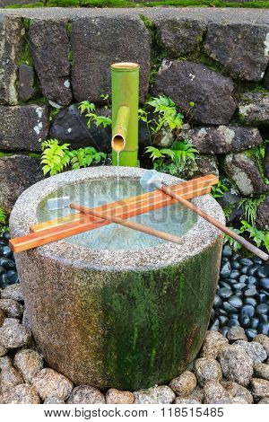 Water running out through bamboo pipe to stone water basin. It is to purify oneself before visiting shrine in Japan