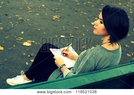 Beautiful Brunette Girl Sitting On The Bench And Writing Into A Diary