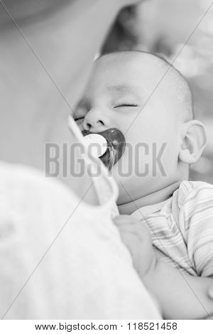 Sleeping Baby With A Pacifier In Mother's