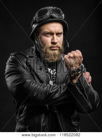 Angry Bearded Biker Man In Leather Jacket And Helmet Over Black Background.