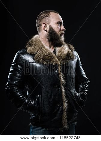 Brutal Handsome Unshaven Man With Long Beard And Moustache In Black Fur Coat With Collar.
