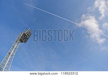 Stadium Spotlights With Airplane Across Blue Sky