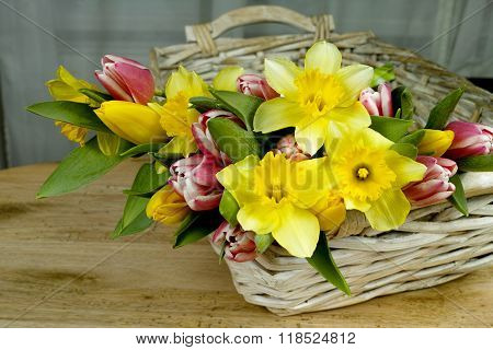 Multicolored Bouquet Spring Flowers With Wicker Basket On Wooden Background