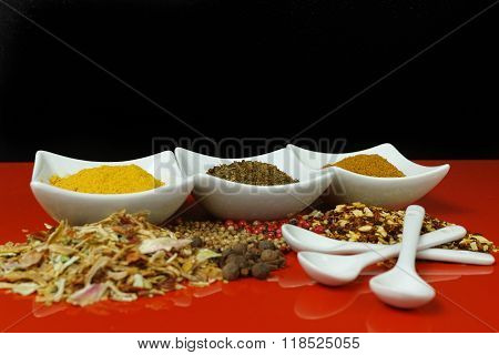 Set Of Spices And Seasonings With White Spoons, White On Red And Black