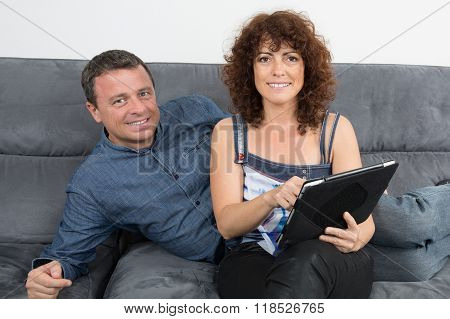 Mid Aged Couple At Home Websurfing On Internet
