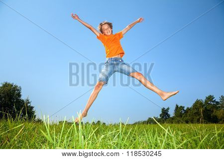 Kid jumping on the sunny meadow in a summer