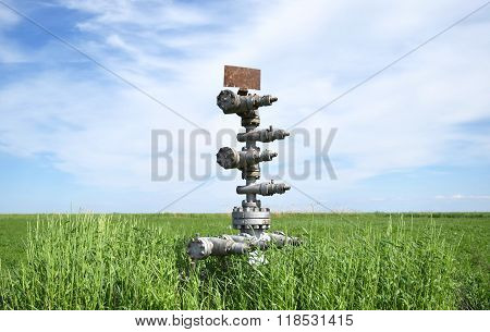 Canned Oil Well Against The Sky And Field