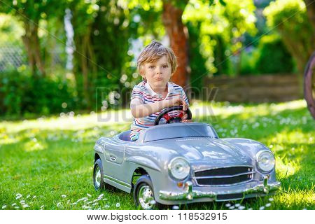 Little preschool kid boy driving big toy old vintage car and having fun outdoors. Active leisure with children during school holidays on warm summer sunny day.