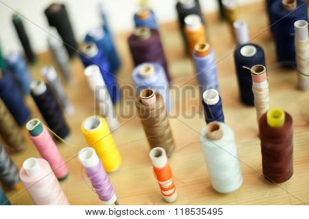 Group Of Sewing Threads On Wooden Board