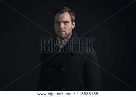 Stubbly Bearded Young Man Wearing Dark Blue Winter Coat.