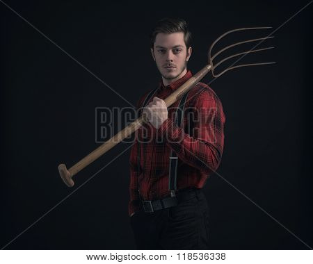 Young Fashionable Farmer In Red Checkered Shirt Holding Hayfork.