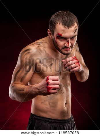 Strong muscular boxer. A man in a boxing stand. Blood on face. Ready to fight