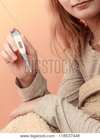 Sick Woman Under Blanket With Digital Thermometer.