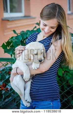 Woman Keeping White Labrador Puppy