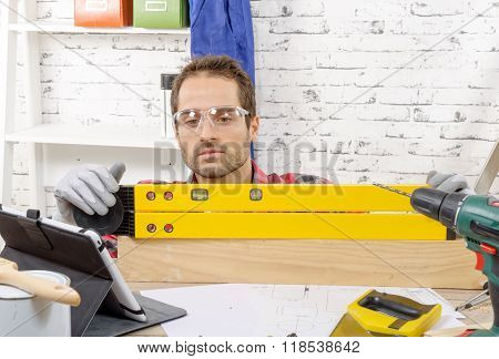 Young Man Viewing A Spirit Level,  To Read The Position Of The Bubble To Ensure A Horizontal Line
