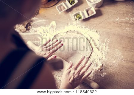 Whole grains.Dieting.Cooking food at home.Woman preparing dough on table in the kitchen.Pizza crust