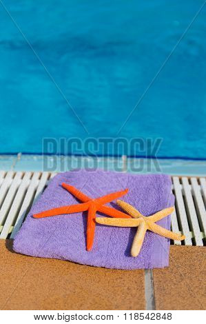 Towel and star fishes at the swimming pool