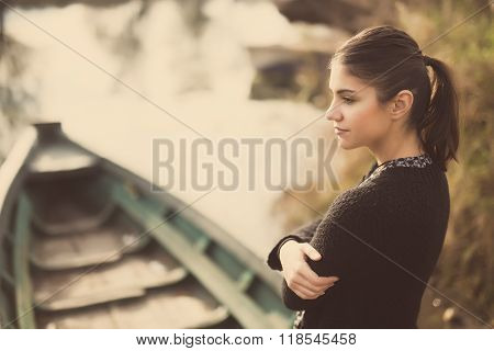 Girl at the old fishing boat looking to the lake.Melancholia sadness sorrow concept.