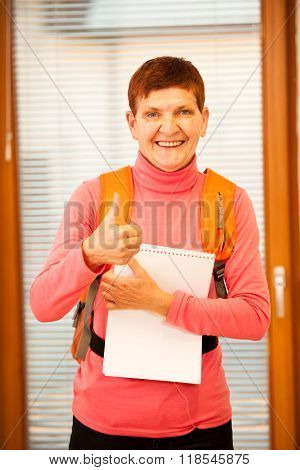 Older woman representing lifelong learning. Woman with school bag smiling and showing thumb up as a gesture of happiness and joy of learning.