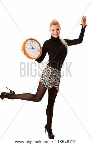 Calm smiling woman with big orange clock gesturing no rush enough time to be punctual.