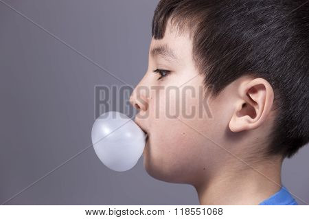 Close Up Of Boy Blowing Bubble.