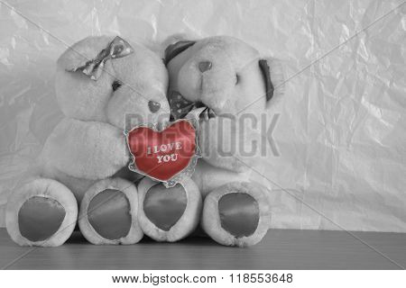 Two bear dolls holding red heart