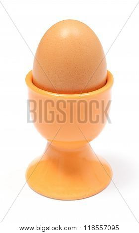 Closeup Of Boiled Egg In Orange Cup. White Background