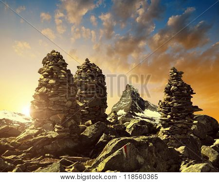 Stack of rocks stones at sunset in the background Matterhorn - Pennine Alps, Switzerland