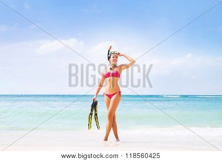 Gorgeous, happy lady in alluring pink bikini posing with diving mask and flippers on the beach.