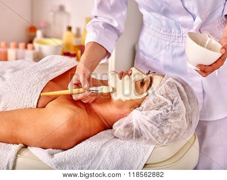 Woman middle-aged look up take facial and neck clay mask in spa salon. Two female people.