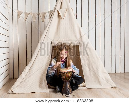 little girl with drum near wigwam playing Indian
