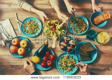 Top view of family having dinner together sitting at the rustic wooden table. Enjoying  family dinne