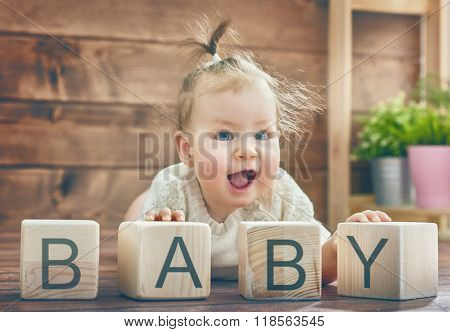 Happy child baby girl playing with blocks and having fun. Blocks have letters. The child puts the word Baby.