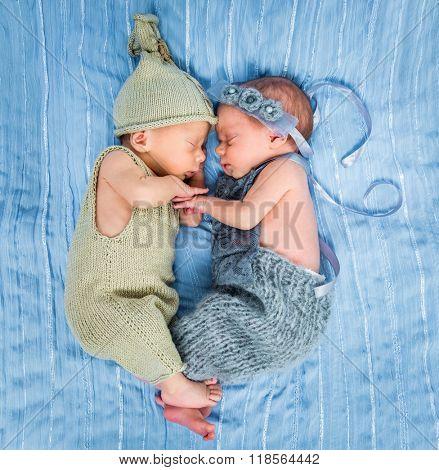 newborn twins - a boy and a girl sleeping on a blue blanket
