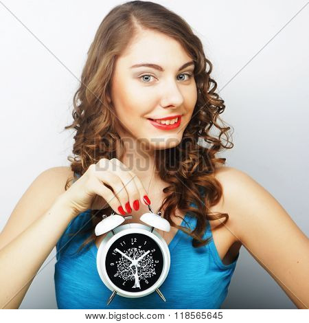 Young happy curly woman with alarmclock