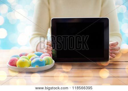 easter, holidays, technology, advertisement and people concept - close up of woman hands with tablet pc computer and easter eggs
